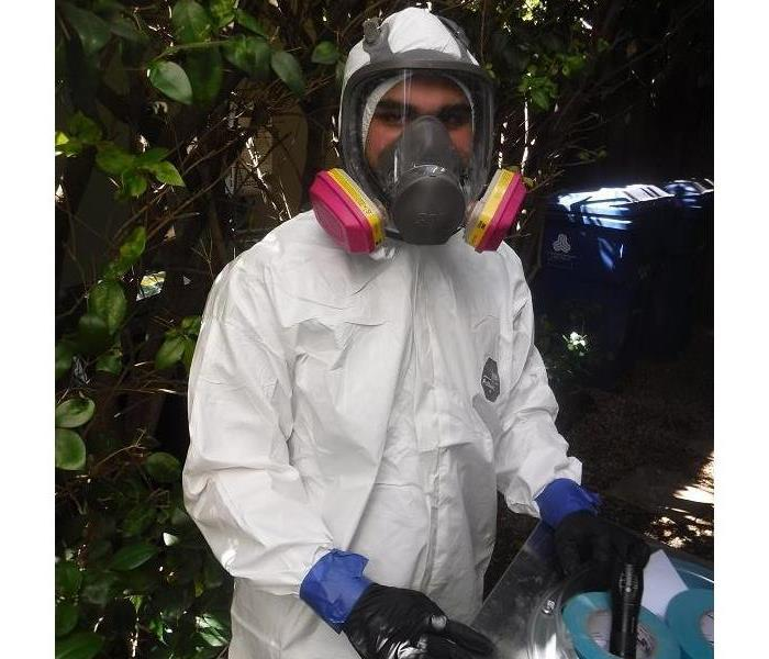 Suited up employee going to help clean